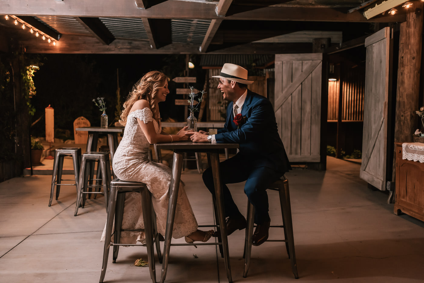 Classy bride and groom take a seat at the rustic bar area of The Homestead at Wilshire Ranch.