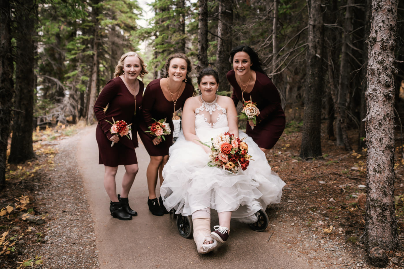 Bride poses with her bridesmaids as they travel down the trail to the ceremony site at Switcurrent Lake.
