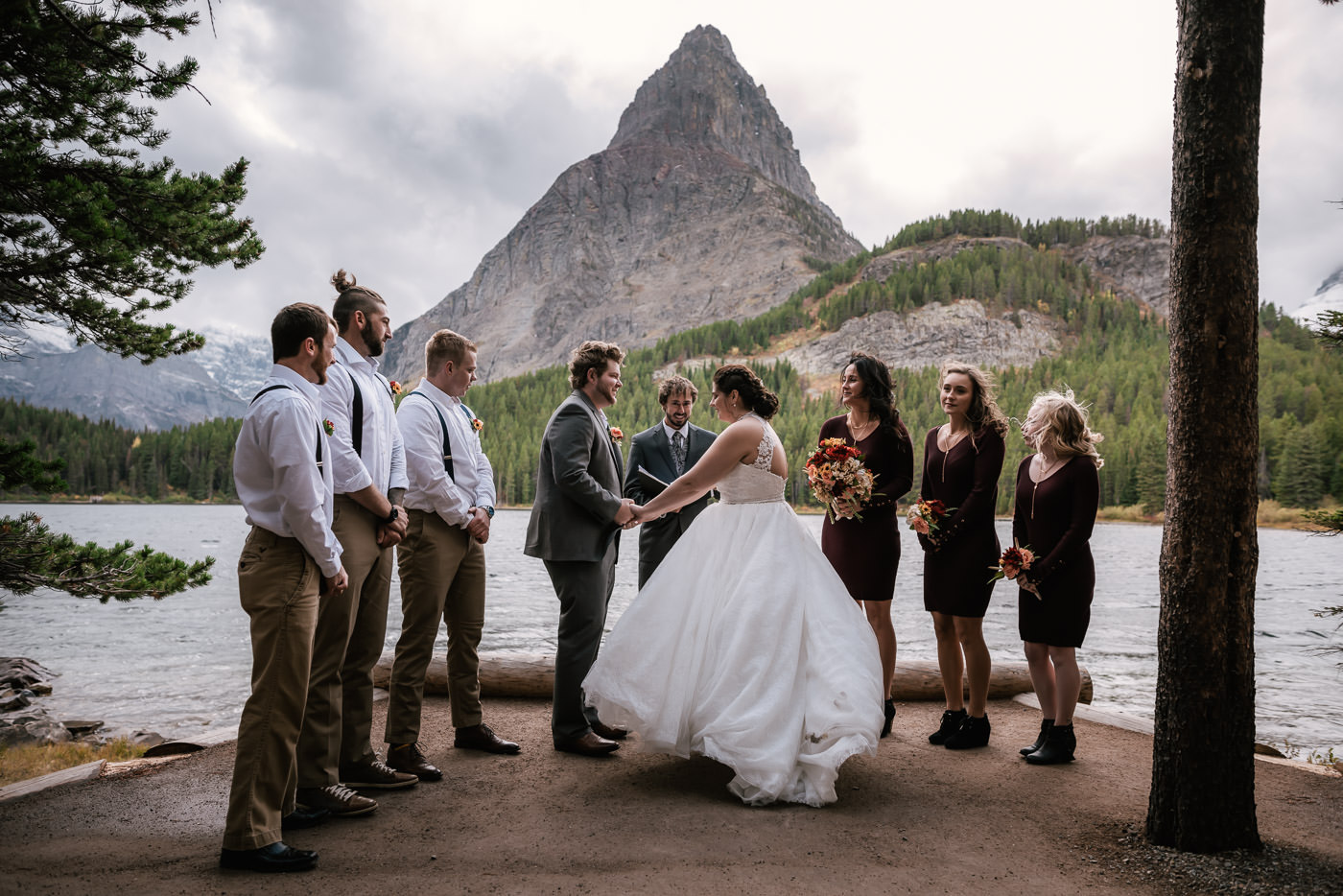 Glacier National Park elopement photogrpaher captures a couples touching ceremony on the shores of Swiftcurrent Lake in Many Glacier.