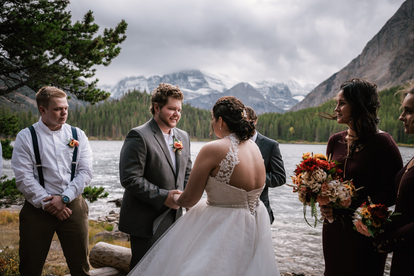 Groom smiles at his bride as they exchange their vows in Glacier National Park.