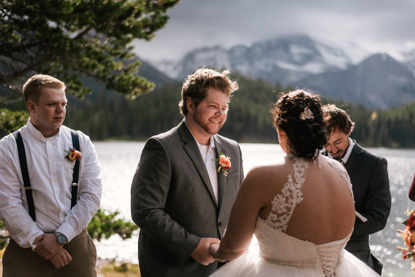 Groom is glowing with happiness as he marries his best friend on the shores of Swiftcurrent Lake.
