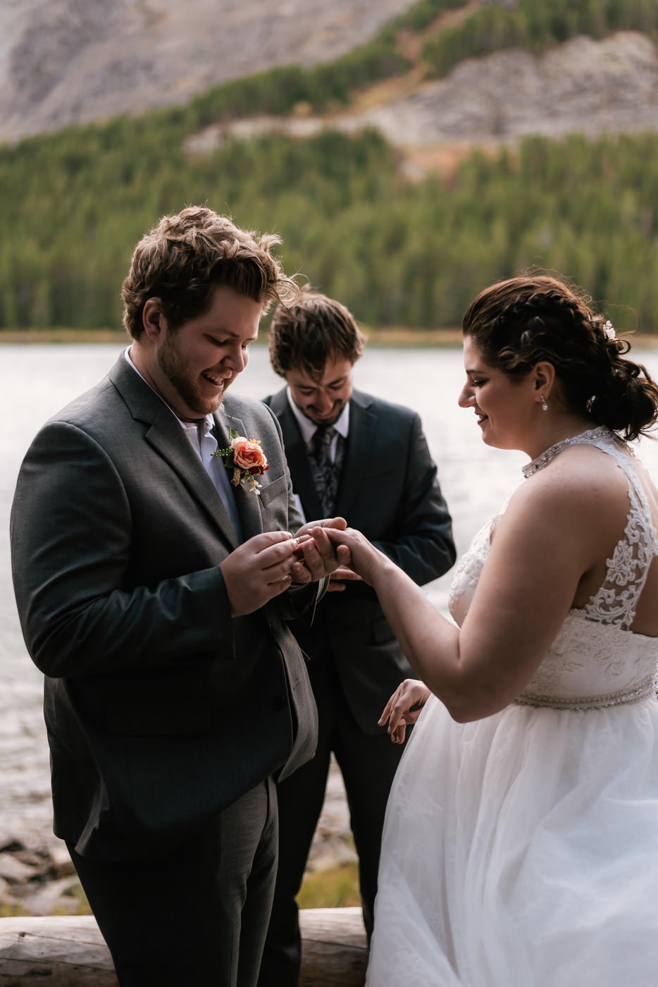Groom slips the wedding ring onto his new wife's finger at their glacier elopement.