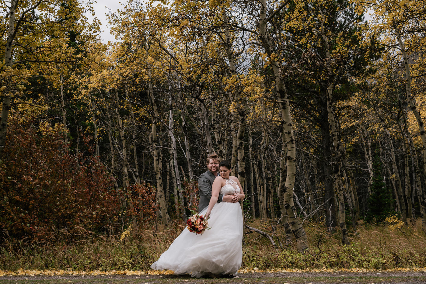 Groom wraps his arm around his bride in front of a birch forest with fall color in Many Glacier.