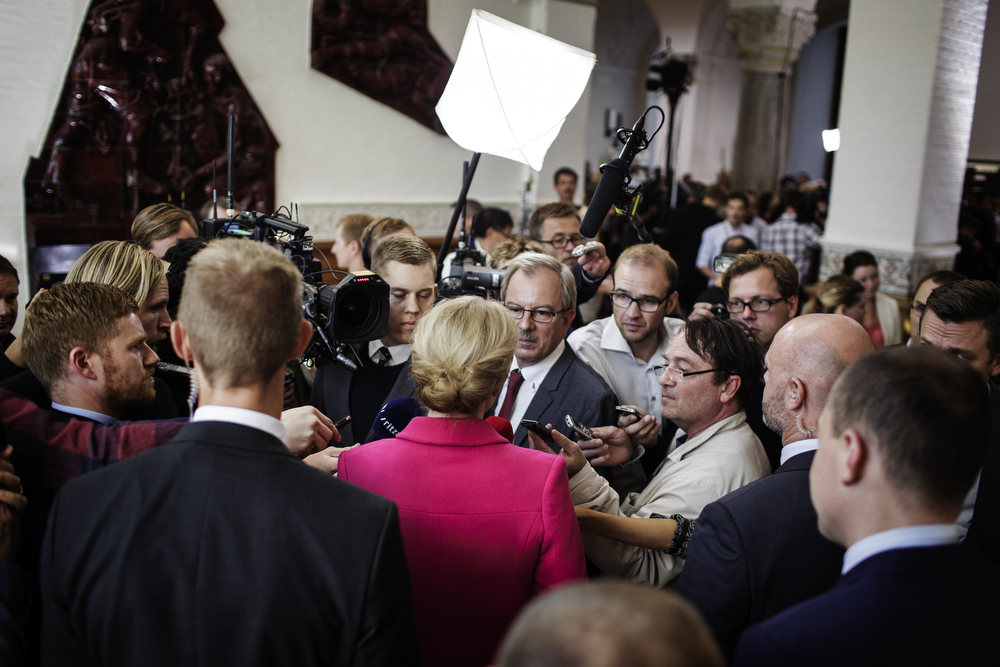 The PM is the natural center of attention for the journalists.