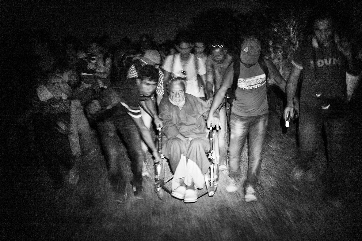Faiz is quiet while the large group of men pushes the wheelchair over the border into Hungary at the small crossing point near Röszke on September 2nd 2015. Shortly after the front wheel of the wheelchair gets stuck once again in one of the many holes in the small gravel road. Faiz hand squeezes the armrest extra tightly while the men around him struggle to get the chair free.Faiz is 75 years old and has come all the way from Deir ez-Zur in Syria with his two daughters Mariam and Hamda and his grandson Murhaf. They have been on the road for almost a month and has now crossed the border to Hungary. Sweden was the family's intended destination, but since he wheelchair is starting to come apart they have to register with the Hungarian authorities. Afterwards, they are planning to continue onwards to Germany, where the rumors say, they can get asylum despite having been registered in Hungary.