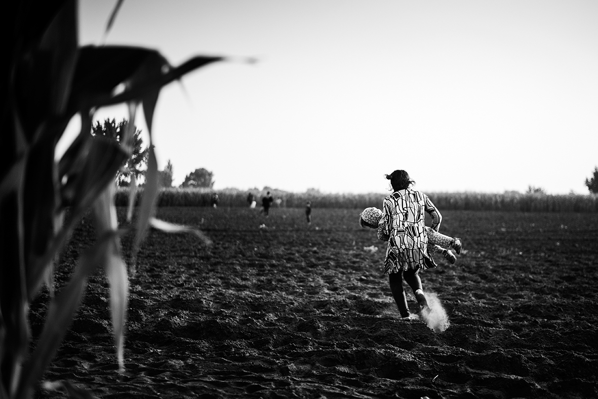 With her daughter in both arms Suzanne runs across a bare field after having crossed the border into Hungary on the train tracks near the border town Röszke on September 1st 2015. She is trying to hide from the Hungarian police in the cornfields on the other side. Eight adults and six children from Syria has crossed one of the unofficial border crossings used by refugees to get from Serbia to Hungary and now the family is trying to get through Hungary without getting registeret by the authorities. They don't want to risk being sent back to this country, when they reach their final destination: Germany, Sweden or Denmark.In 2015 over 1 million migrants and refugees entered into Europe according to the International Organisation for Migration (IOM). An amount of people that seemed to take the European nations by surprise and resulted in a lot of debate between the countrys as to how many refugees the individual countries should take in. During the summer Hungary tried to stop the flow of refugees by constructing a 175 km fence along their border with Serbia witch only resulted in redirecting the flow of people through Croatia instead. The year passed, and the politicians didn't manage to come up with a viable solution to the refugee crisis in Europe. With no end in sight for the war in Syria or the other conflicts around the world, the refugees keep coming.