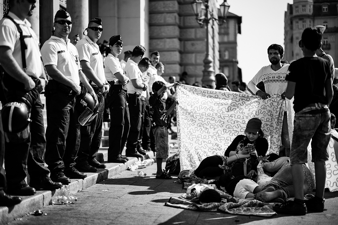 A small group of men is trying to shield woman and children from the harshest afternoon sun on the square in front of the central Keleti train station in Budapest. It's September 1st 2015 and the Hungarian police has temporarily stopped all train traffic. They have also cleared the station building in an attempt to regain control of the large number of refugees trying to get on one of the trains going to countries like Austria and Germany.