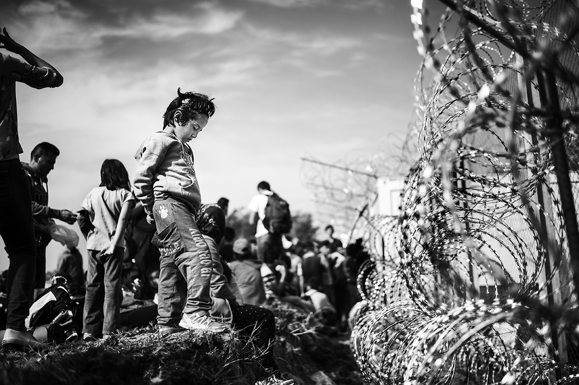 A young girl looks into Hungary from 'no mans land' on the Serbian side of the border near the motorway border crossing on E75. It's the morning on Septemer 15th 2015, and last night the Hungarians closed their borders for all refugees trying to cross on their way to Northern Europe.Over the summer a 175 kilometer barbed wirer fence was erected along the Hungarian border to Serbia to stop the flow of refugees.