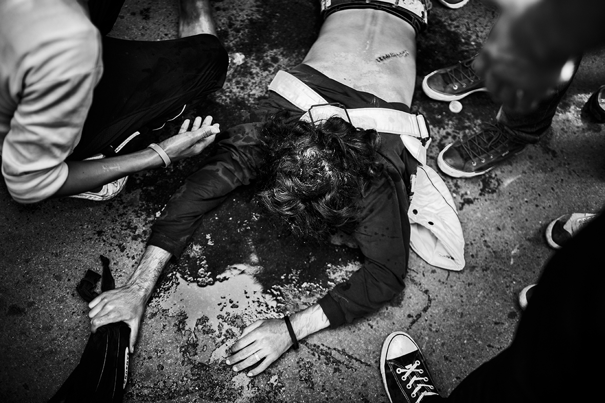 A young man is unconscious, after he was hit in his head during a fight between Syrian and Afghan refugees on September 18th 2015 at the railway station in the Croatian city Beli Monastir. Overnight the city received more than 2000 refugees - according to a local policeman three times the number expected by the local authorities - and the situation develops chaotically in the morning, when the thousands of people realizes, that there aren't enough bus- and train tickets for everyone.