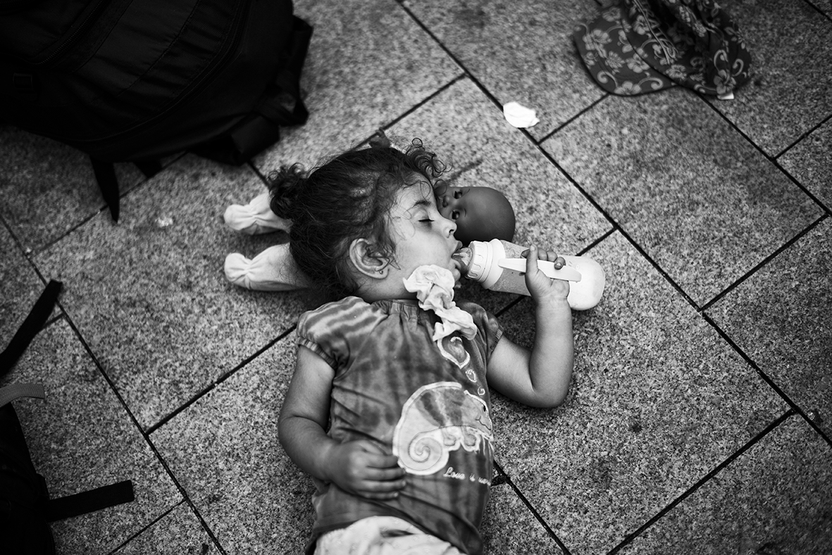 A little girl is sleeping on the pavement in front of the Keleti train station in Budapest on September 1st 2015. Thousands of people are forced to stay on the street, when the Hungarian police shuts down all trains going north and evacuates the station building in order to regain control. A large number of people has been staying inside the station while waiting for a chance to get on a train further north. Most of them wanting to go to either Austria or Germany. 