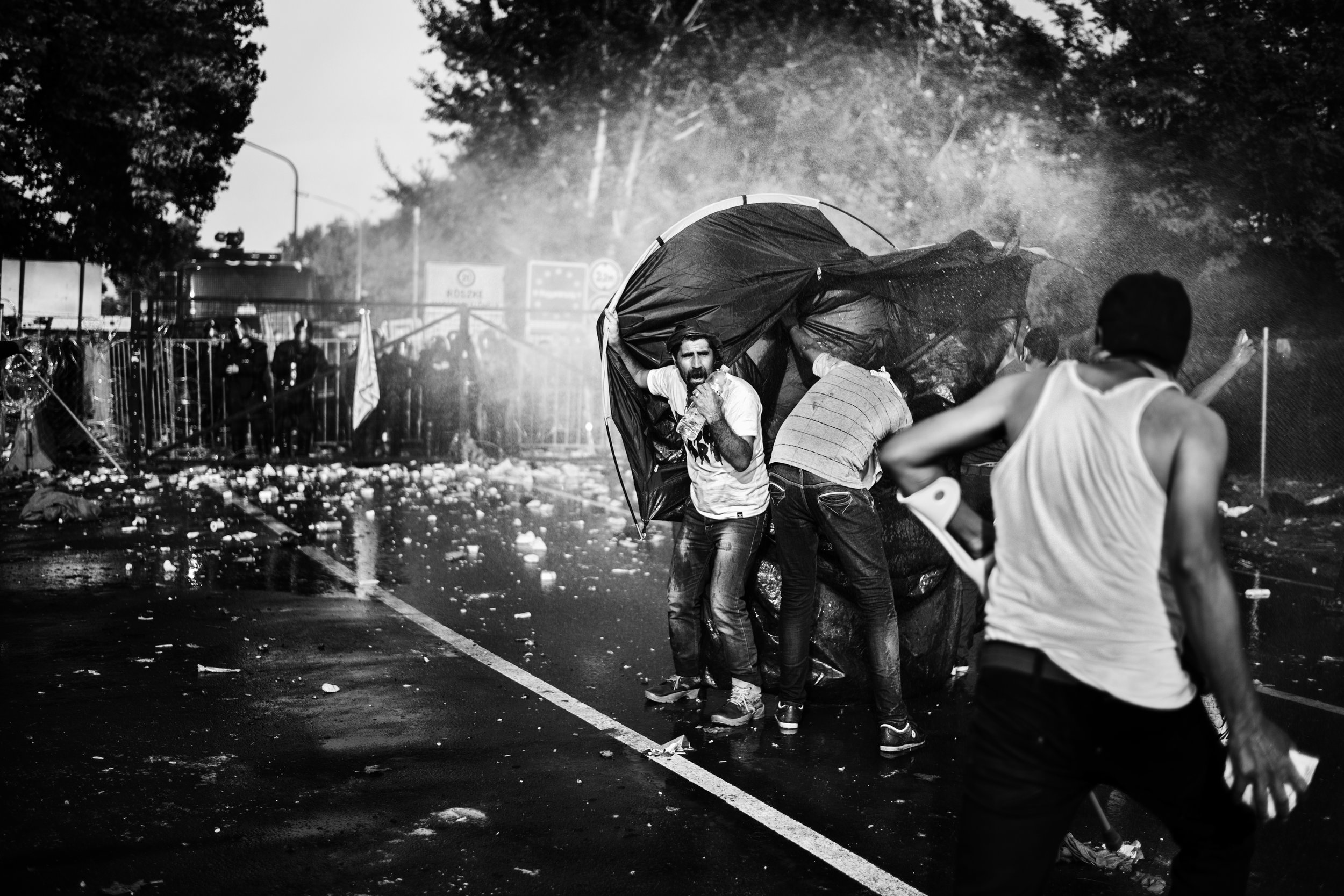 A group of refugees on the closed border-crossing between Serbia and Hungary uses a tent as their shield against the water canon and teargas canisters coming at them from the Hungarian police on September 16th 2015. The atmosphere has been tense for about 36 hours, when riots finally break out between refugees on one side of the border and Hungarian police on the other.