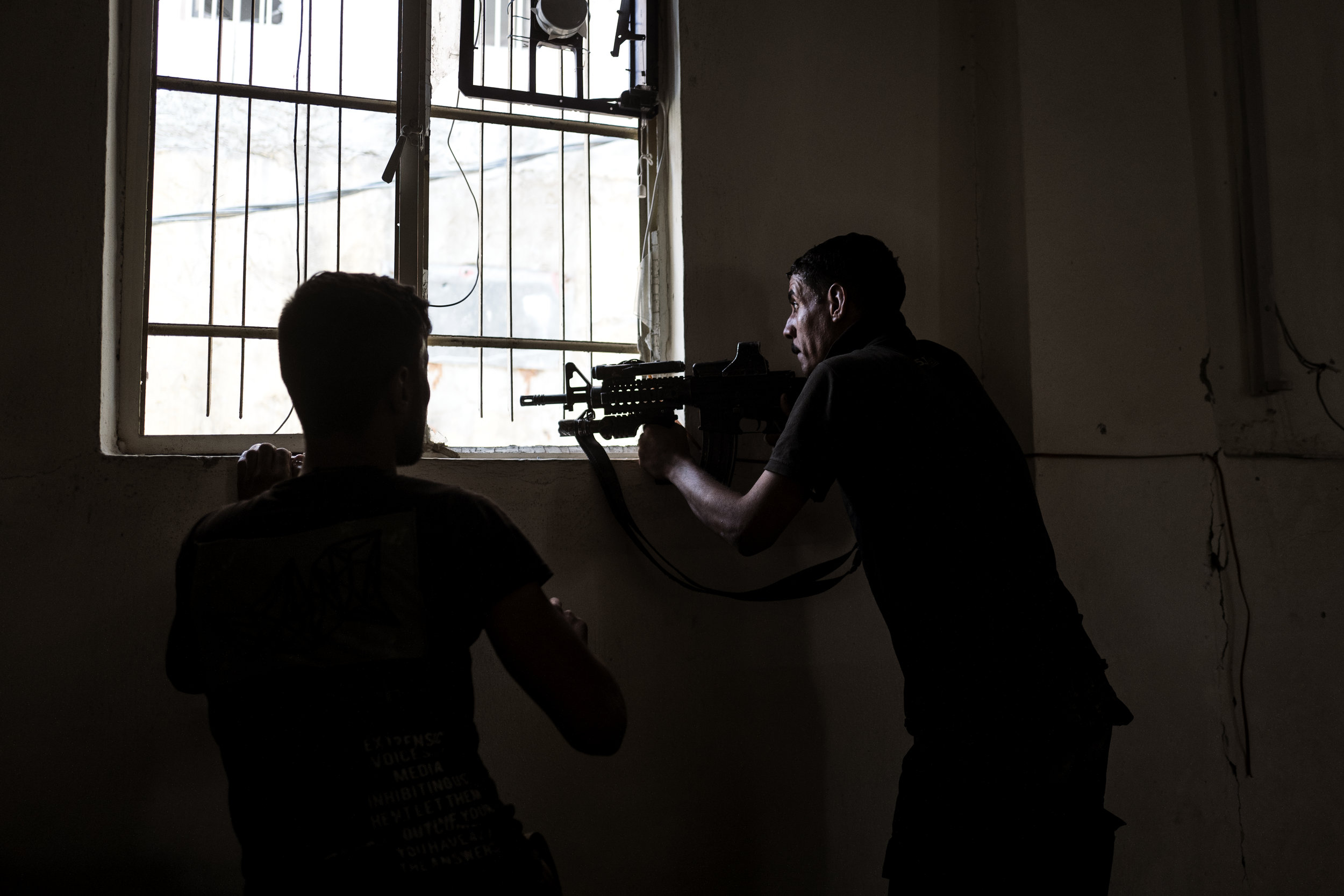 20 meters. So short is the distance between Muhamed Yasin and the house across the street, where a groupe of ISIS fighters have barricaded them selves in the middle of Mosul's Old City. Muhamed is waiting ready with his M4 automatic rifle. He can hear the enemies talk, but he cant see them. Muhamed Yasin is a soldier in the I.C.T.F. also known as Golden Division. The narrow streets of Mosul often make it impossible for the Iraqis to use their armored vehicles, so the soldiers are fighting on foot from house to house.