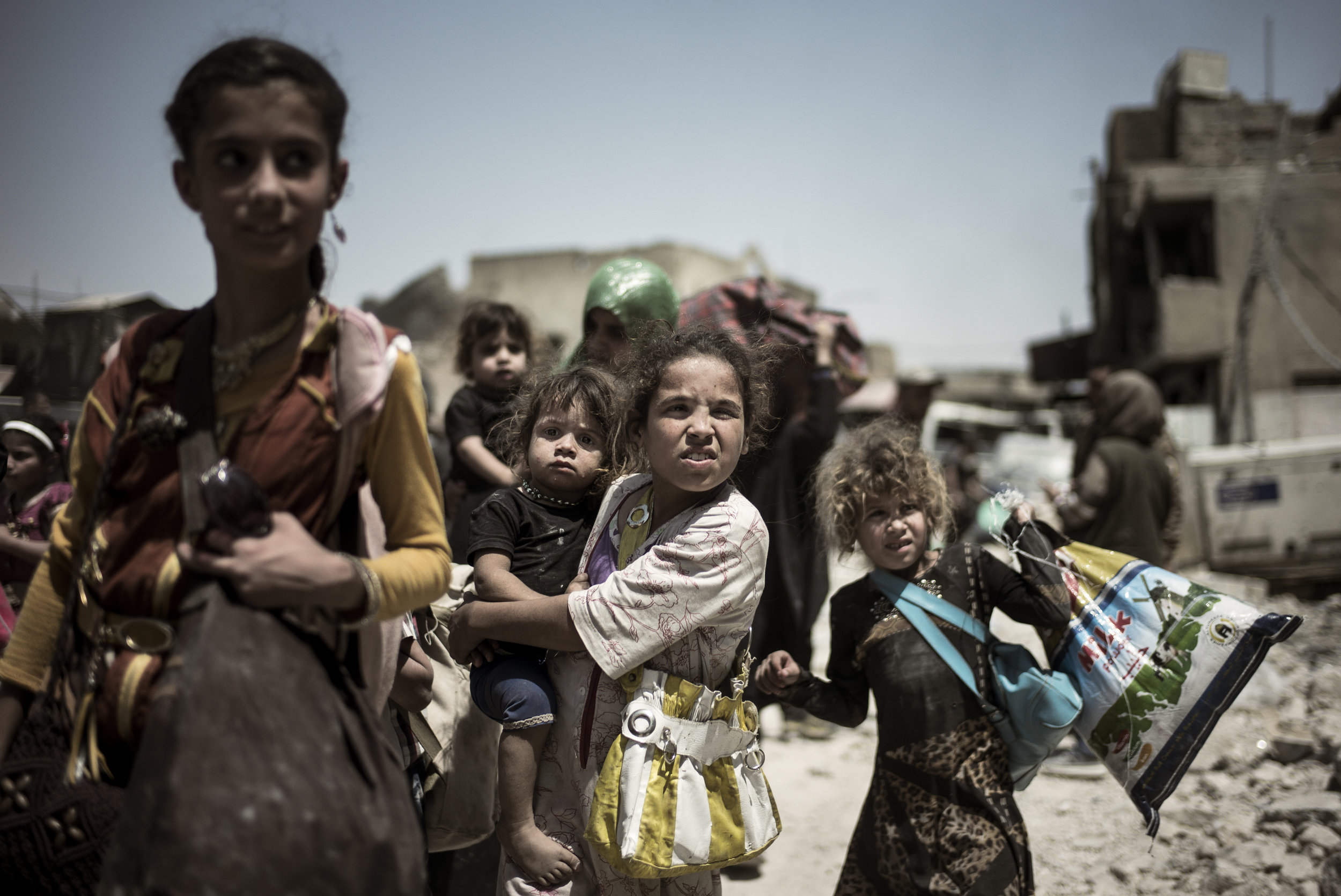 During a break in between fighting and mortar shelling civilian men, women and children take the opportunity to escape their homes and the war zone, where they have lived under siege for weeks and months.