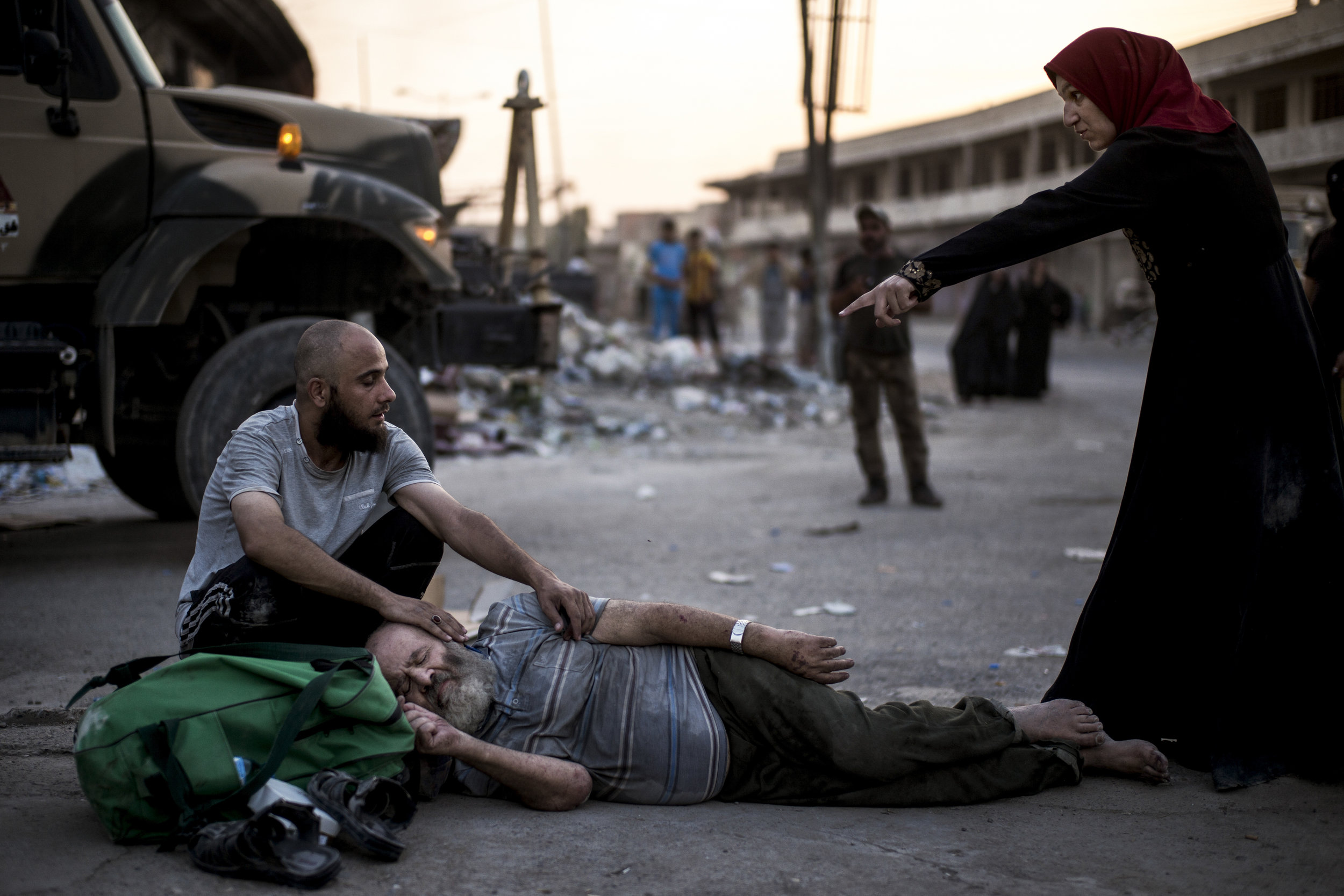 Ahmed Hamid Issa lies exhausted in front of the gate to the Iraqi military intelligence field headquarters. He cant walk, so two younger men have carried him the final distance. To make sure no ISIS fighters escape all men that make it out from the frontlines are questioned by the intelligence officers.