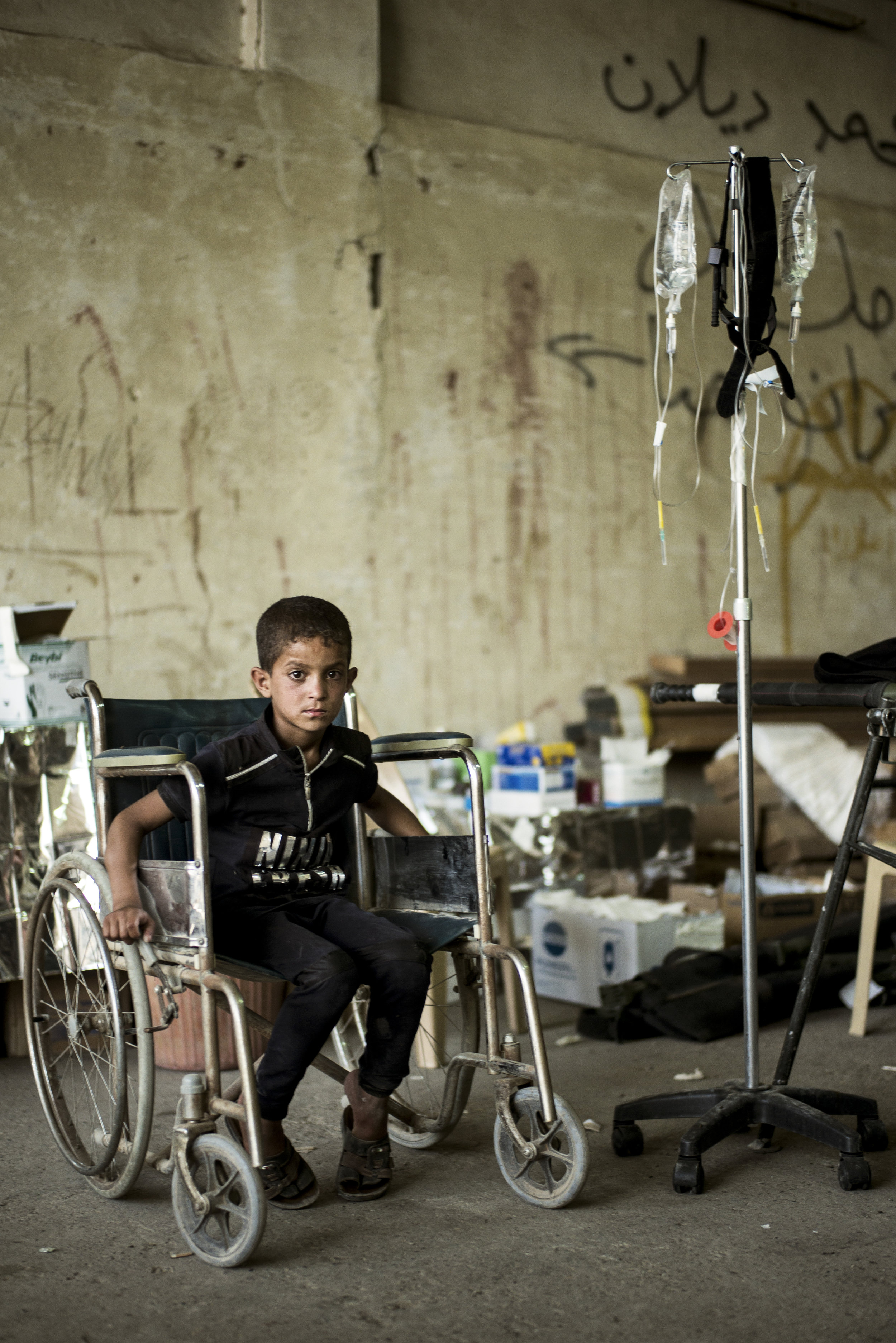 A boy playing in a wheelchair at the field hospital near the front lines in Mosul.