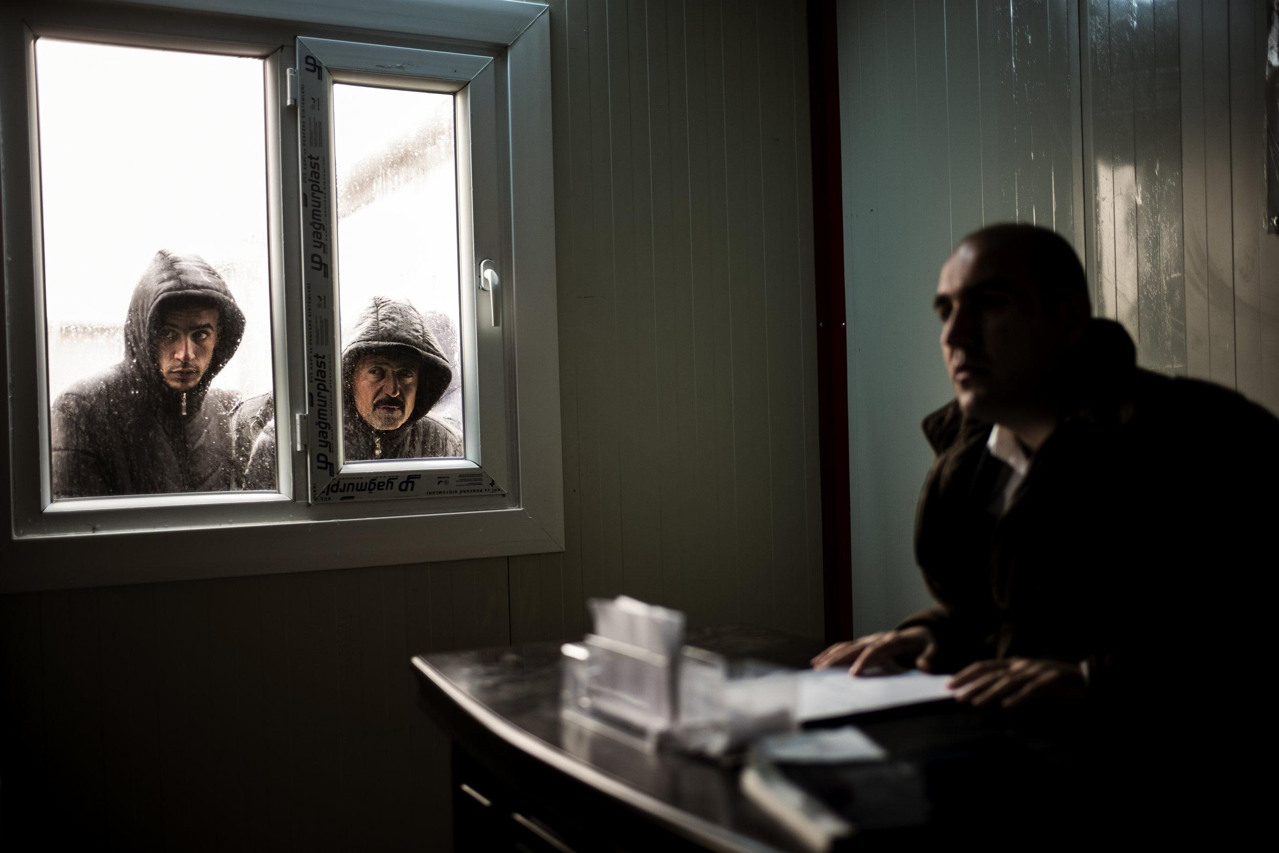 Ekstra Bladet i Mosul: To beboere i Khazer flygtningelejeren kigger gennem vinduet til lejerens leder. Efterhånden som flere af lejerens indbyggere har fået mulighed for at vende tilbage til deres hjem har det givet mulighed for, at store familier kan få et ekstra telt, så de ikke skal bo så trangt. Det kræver dog tilladelse fra lejerchefen.