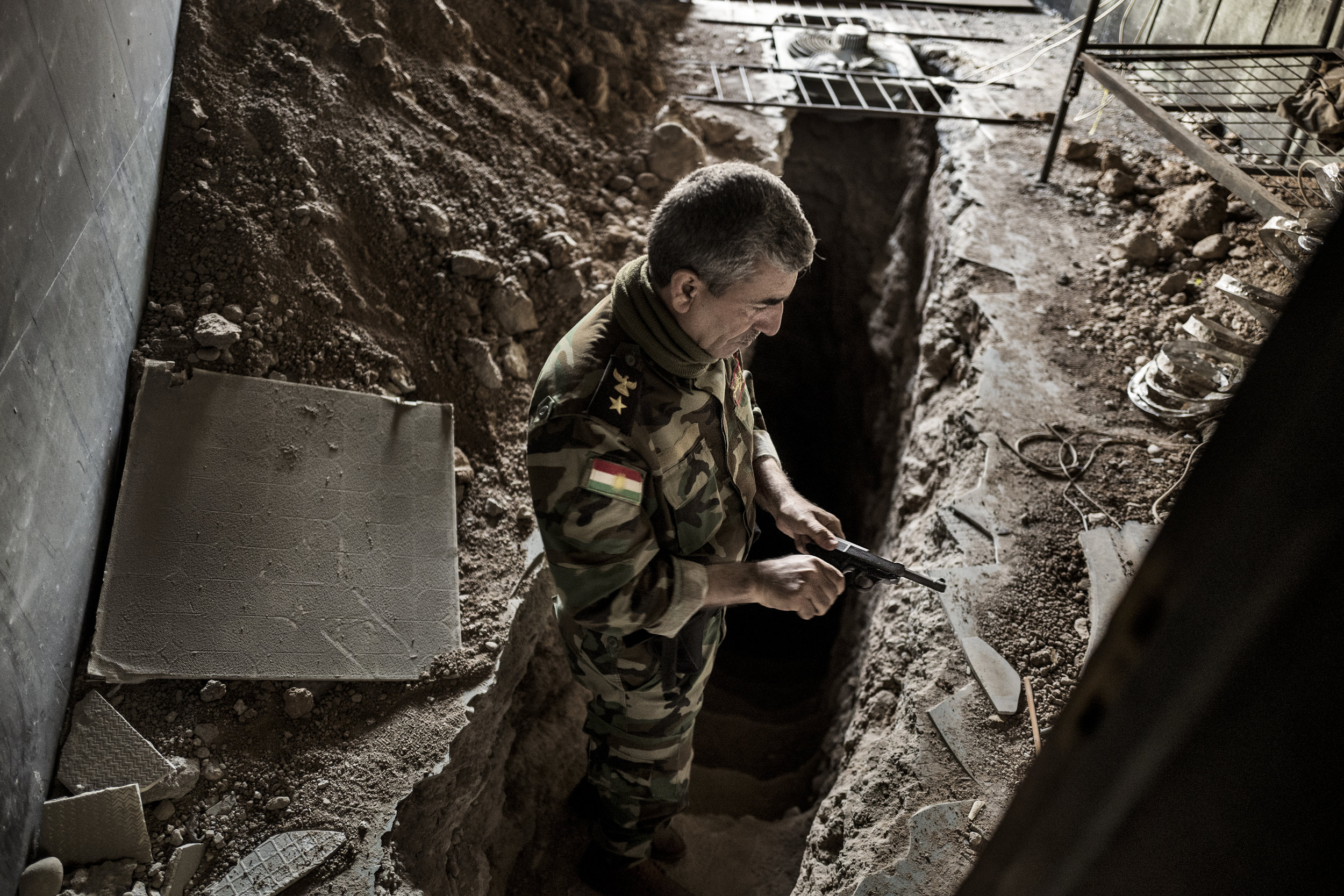 Lieutenant Colonel Mahmood Zkrie from the Kurdish forces readies his gun before heading into one of the ISIS tunnels in the city of Baashiqa 14 km from Mosul. 'You never know, what you run into down there', he says. ISIS dug several tunnels under the streets and houses to get from one part of the town to the other without exposing them selves to coalition fire. Mahmood Zkrie estimates, that this tunnel has taken two months to complete. It's equipped with tv-monitors, so ISIS could monitor the coalition troops on the streets above.