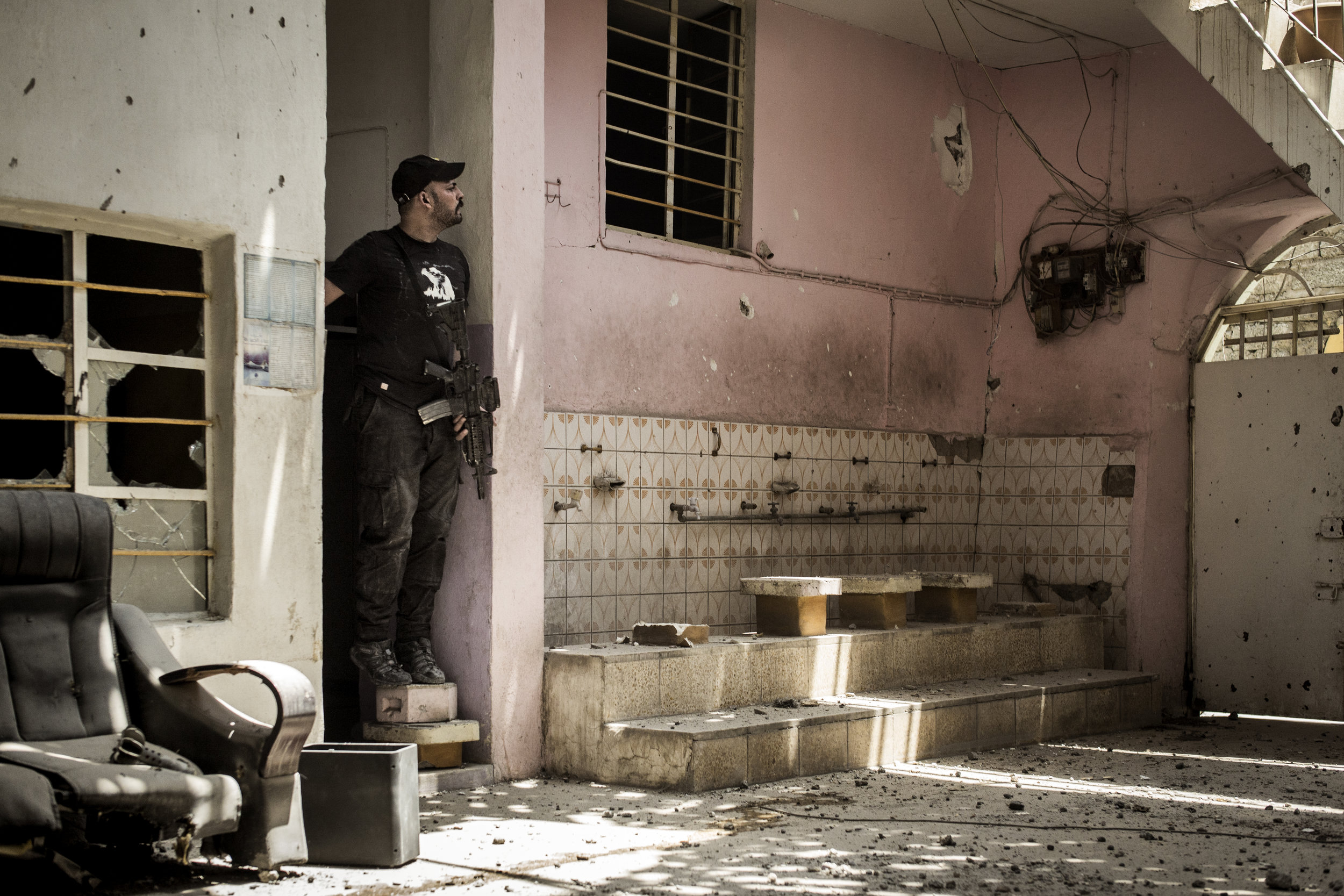 Golden Division soldier scouting for enemy fighters in a building cross the street from an ISIS position.