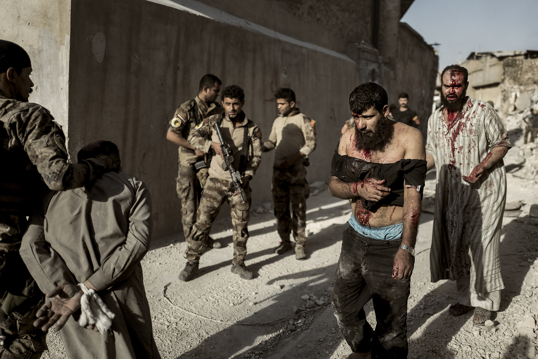 'It's ISIS', one of the soldiers yells, while they lead yet another group of wounded men covered in dust through the rubble of Mosul, away from the front lines.