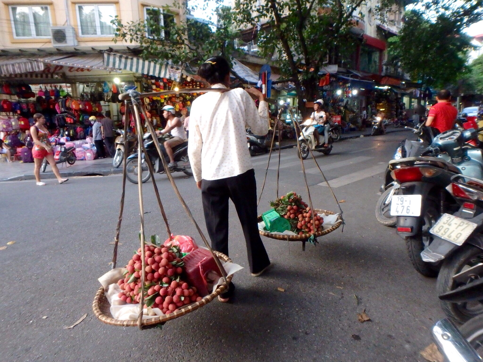 A typical day includes many street vendors selling fruit and many motorbikes crowding the streets.