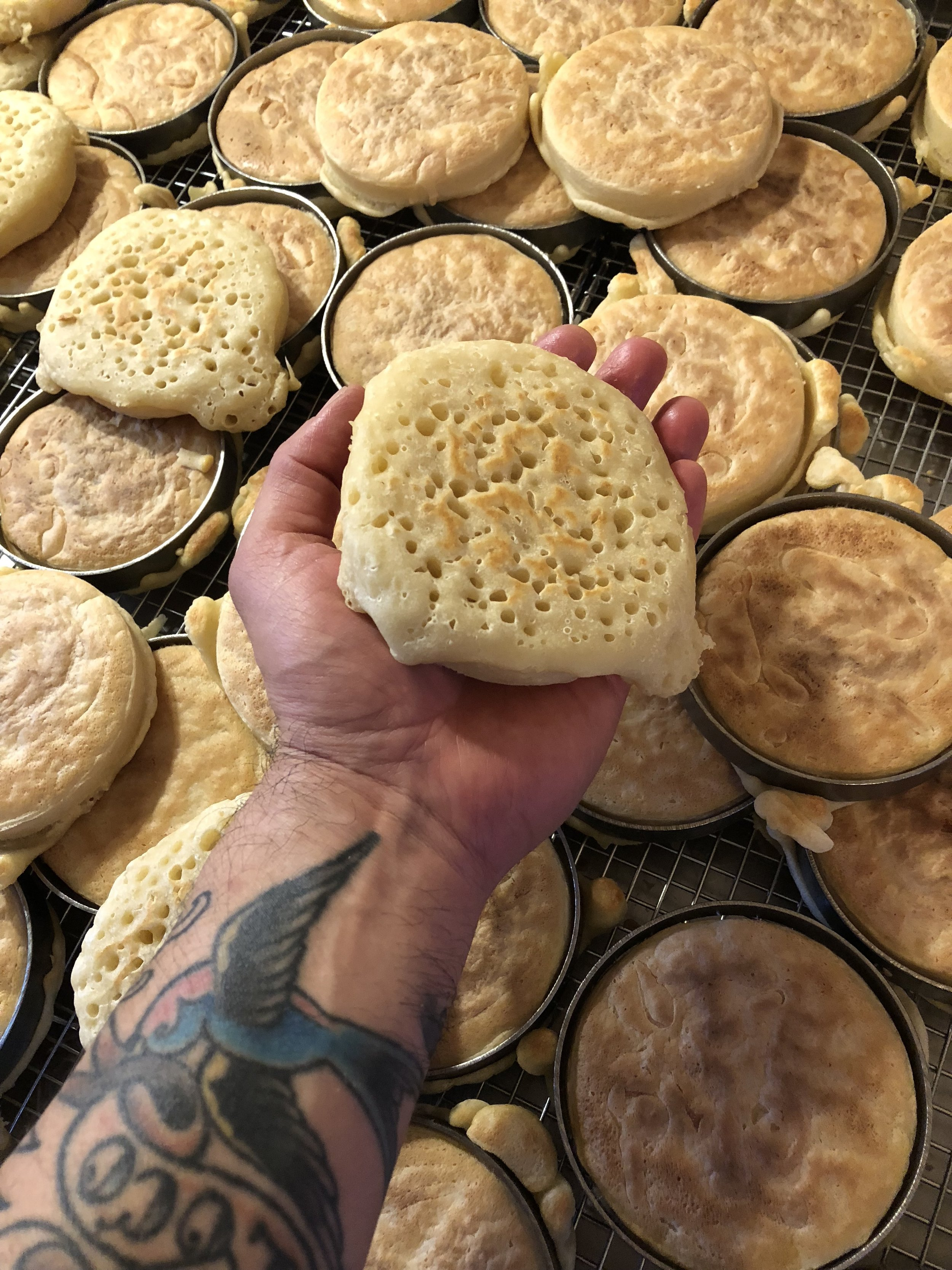 Backside of crumpets, just off the griddle and ready to pop out of the rings.