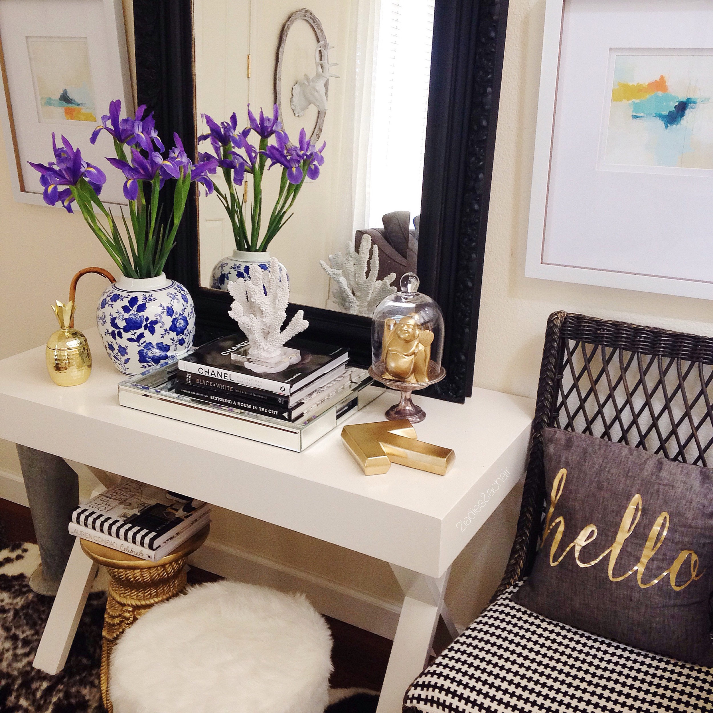 This entryway has many different competing styles: modern artwork, vintage mirror, sleek table, traditional vase, funky stools, and an outdoor wicker chair.