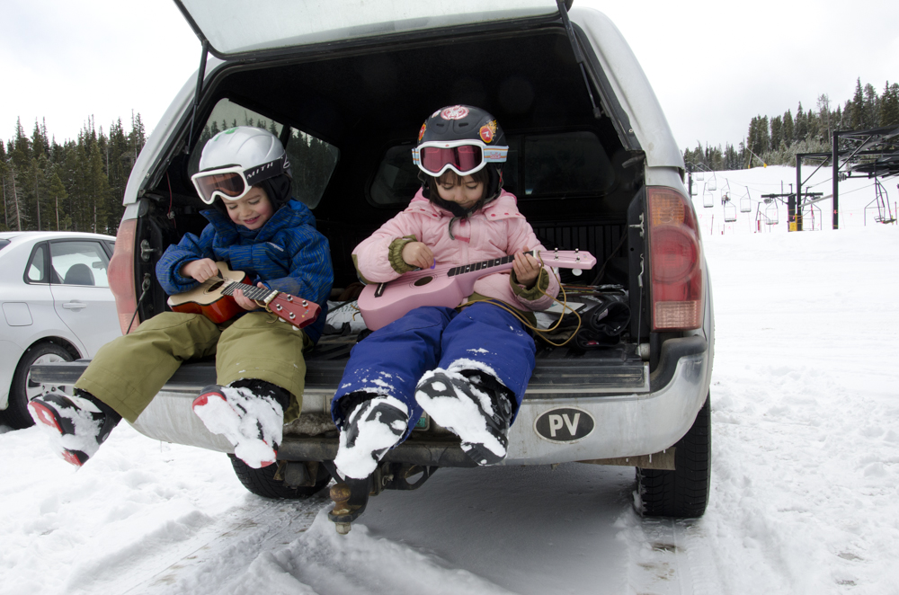 Twin brother and sister jam on their ukeleles after a day of skiing in Colorado. Still wearing ski boots, bare hands in the cold, kids live in the moment.
