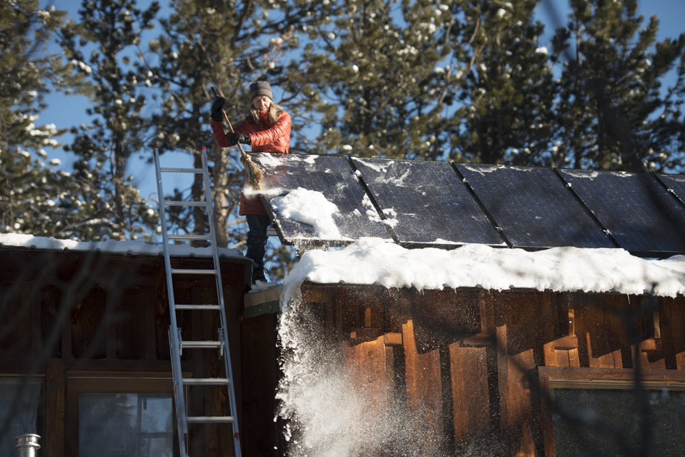 Woman cleans solar panels on off the grid cabin