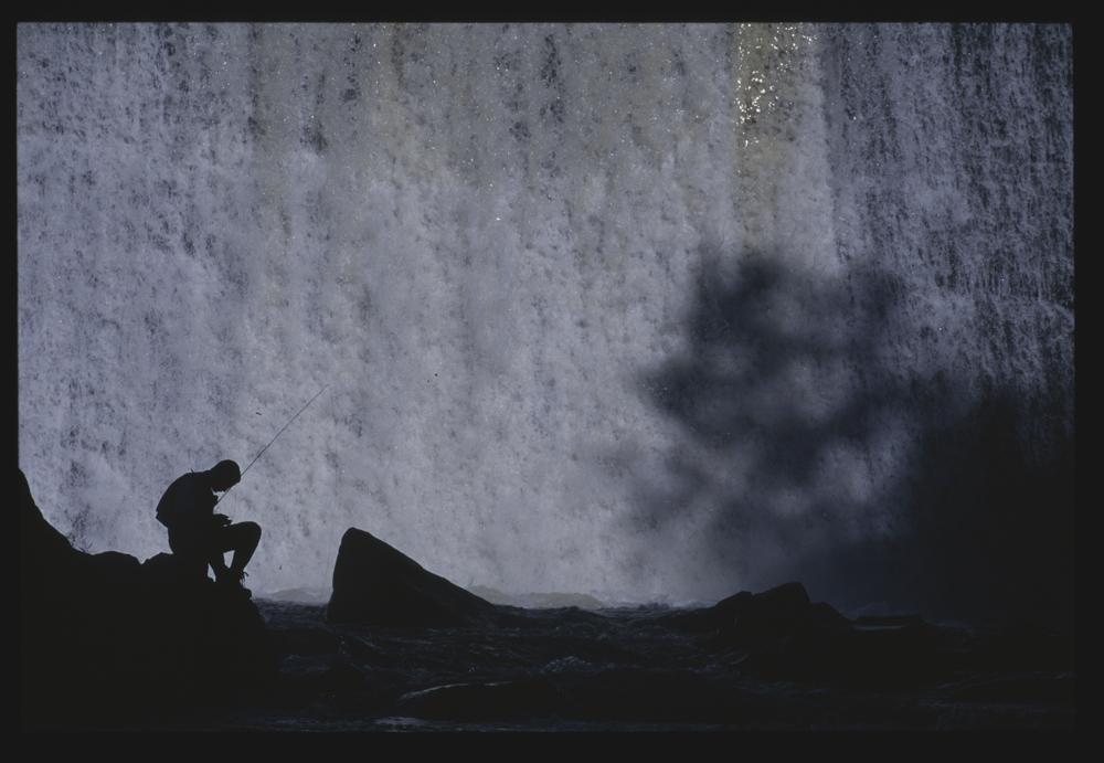 fly fishing near a waterfall