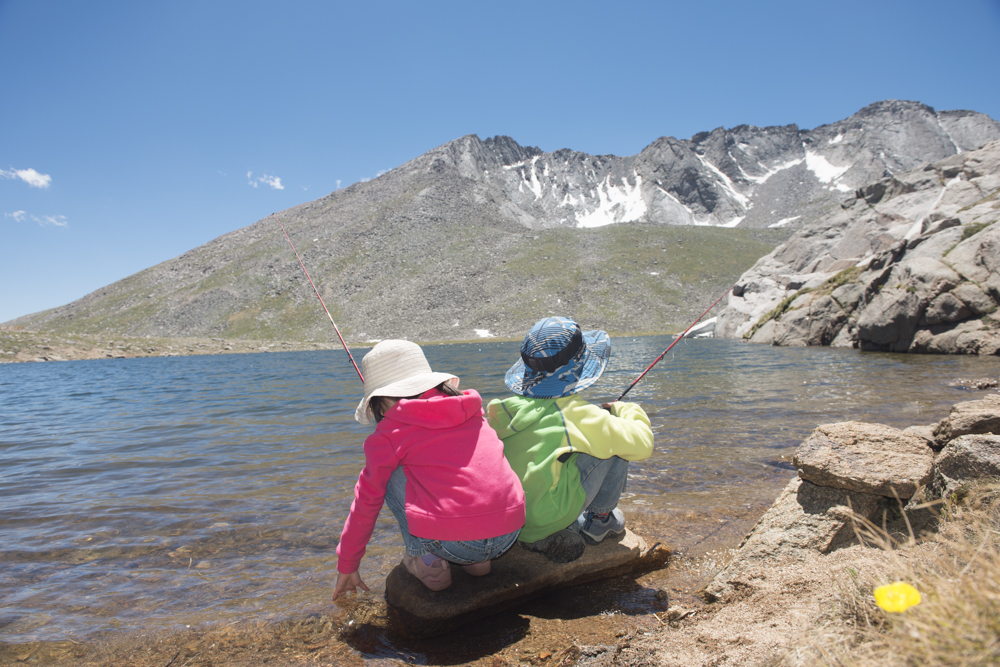 two kids fishing in an alpine lake