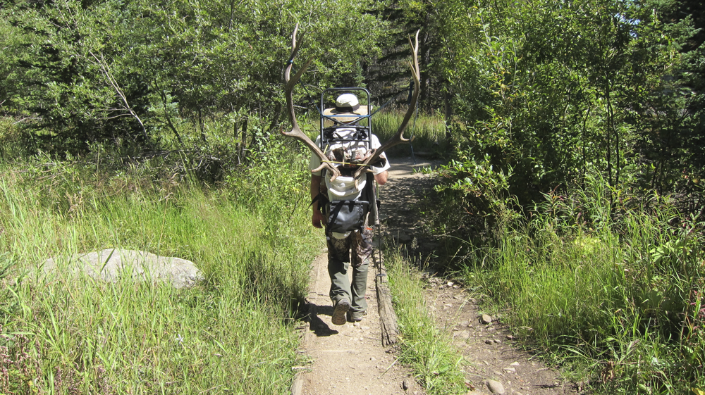 A successful bow hunter with an elk rack