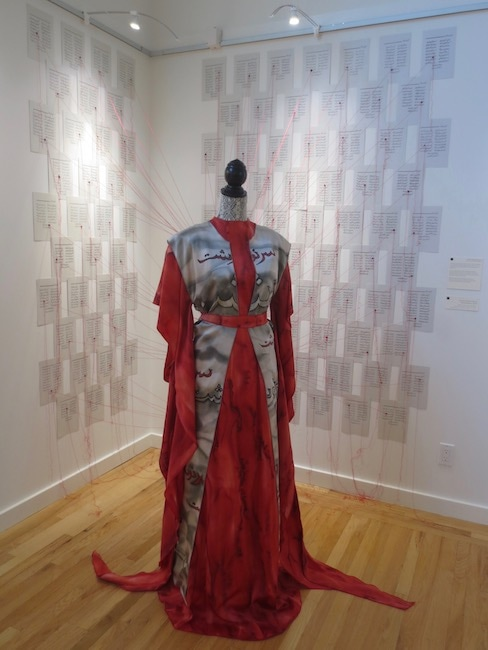 """100 Destinies, 2015,"" by Nazanin Hedayat Munroe. Textile and mixedmedia installation: hand-painted silk gown, dressmaker's form, thread, map pins, and poems of Hafez on cardstock."