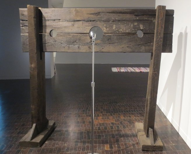 """What Goes Without Saying"" (2012), by Hank Willis Thomas. Wooden pillory and microphone."