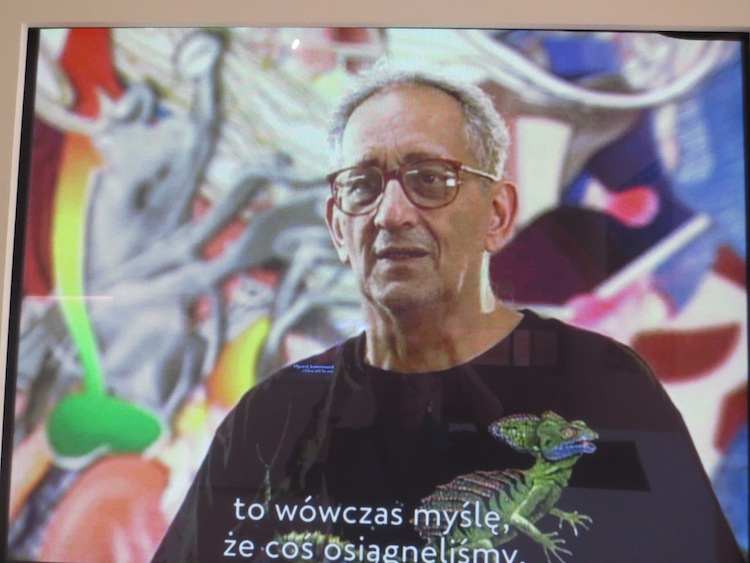 Frank Stella being interviewed at San Francisco Museum of Modern Art, October 2002. Photo of video playing at Polin Museum, Warsaw. https://search.yahoo.com/yhs/search?p=frank+stella&ei=UTF-8&hspart=mozilla&hsimp=yhs-002