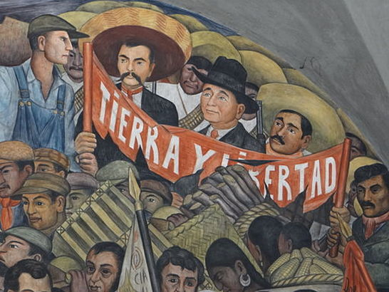"Part of Diego Rivera's ""History of Mexico"" mural at the Palacio Nacional in Mexico City, with images of Emiliano Zapata, Felipe Carrillo Puerto, and José Guadalupe Rodríquez behind a banner featuring the Zapatista slogan, Tierra y Libertad (Land and Liberty). Source: https://commons.wikimedia.org/"