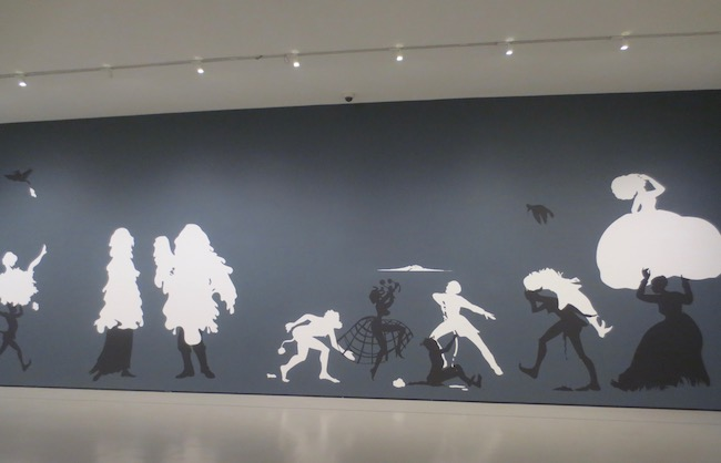 """The Rich Soil Down There"" (2002), by Kara Walker. Cut paper and adhesive on painted wall. Museum of Fine Arts, Boston. In 19th-century American homes, small and delicate silhouettes of loved ones and happy domestic scenes decorated the walls. Finding silhouettes, and racial stereotypes, reductions of human beings, Walker transforms this quaint tradition by turning an entire museum wall into a large tableau of racial and sexual violence in the pre-Civil War South."