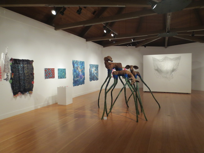 "In the center, ""Phase"" (2016), by Karrie Hovey, needle felted wool. On left wall, ""Memoir 8 - La Ciudad"" (2017), by Laura Raboff, wool and thread. Followed by ""Supplemental 322x"" (2017) and ""Purl 322x"" (2017), handwoven jacquard, hand embroidery, and, on a pedestal, ""Microbiology Lab Series II"" (2016), hand embroidery, all by Ruth Tabancay. Followed by ""Somewhere in Me There Lives Giselle"" (2016) and ""Why Am I not Where You Are"" (2016), quilts of silk and cotton, by Alice Beasley. On free-standing wall, ""Openwork 2"" (2017), made of steel wire by Lily Homer. Berkeley Art Center."