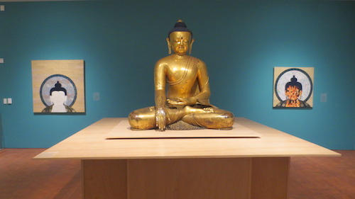 "Two mixed media pieces by Tenzing Rigdol flank a traditional seated Buddha. ""The White Proposal"" on the left; ""Wrathful Dance"" on the right."