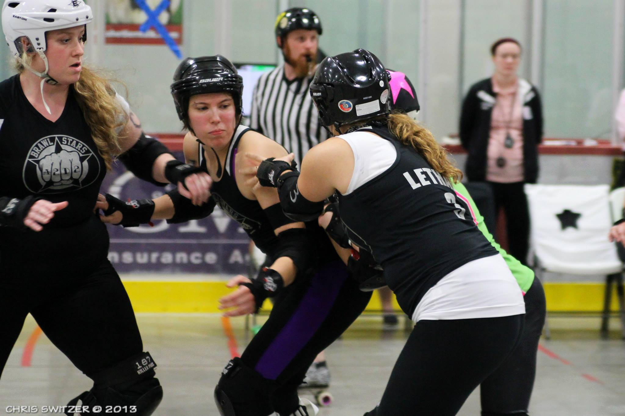 Slamlet is flanked by Brawlstars teammates Courtnasty (left) and Lethal Bo Peep (right) as they block Lansing's jammer during the championship game of the Mitten Kitten Mash-Up North tournament in Kalkaska October 13, 2013. Ultimately, the Brawlstars reigned victorious 256-151. Photo by Chris Switzer.