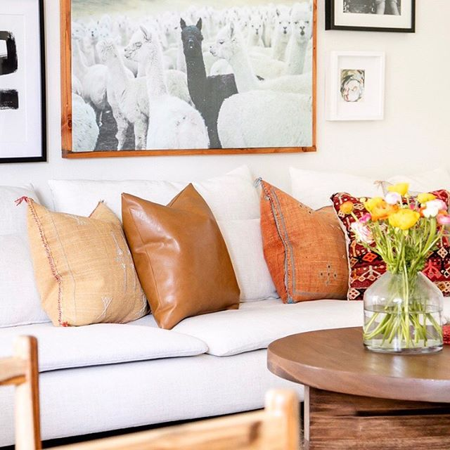 Summer space - bright whites and the perfect mix of color and texture. @rebeccaandgenevieve curated the loveliest textiles and artwork to make her living space feel warm and personal. . Link in bio for the full tour on @glitterguide