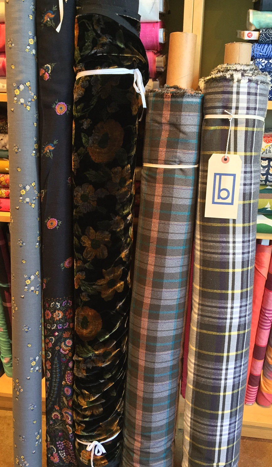 This group offers quite the combination of goodies. On the far left are two very lovely wool/rayon blend prints. These have a beautiful, fluid drape to them. The rayon/ silk velvet in the middle shows off its stunning golden flowers in just the right light, and the two cotton blend plaids are the perfect winter button-up! Check out the Thread Theory patterns on our online store for the Fairfield!