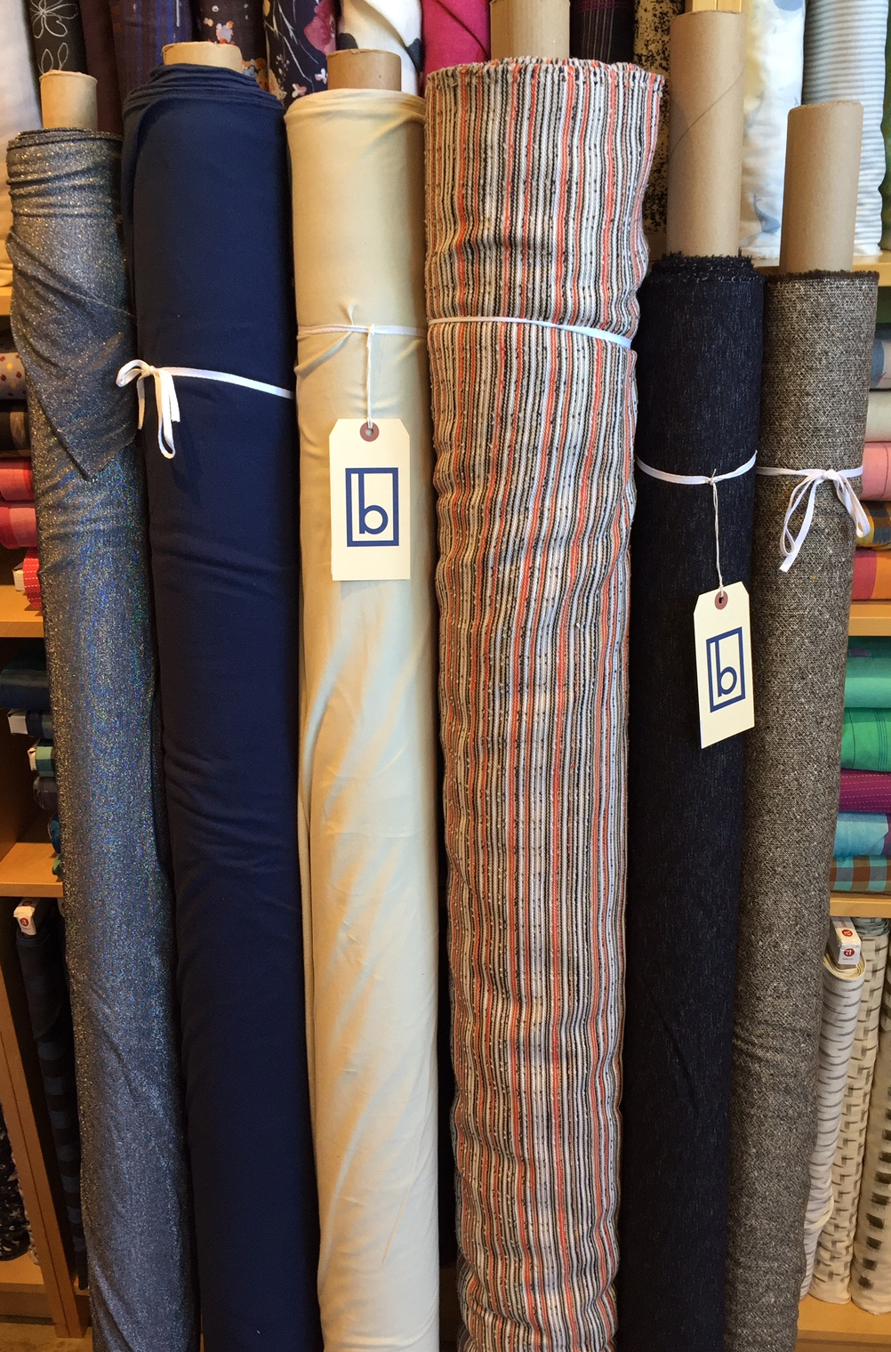 (L to R): Metallic knit, two low loop cotton terry knits with incredible drape and stretch, cotton woven stripe, two wools.