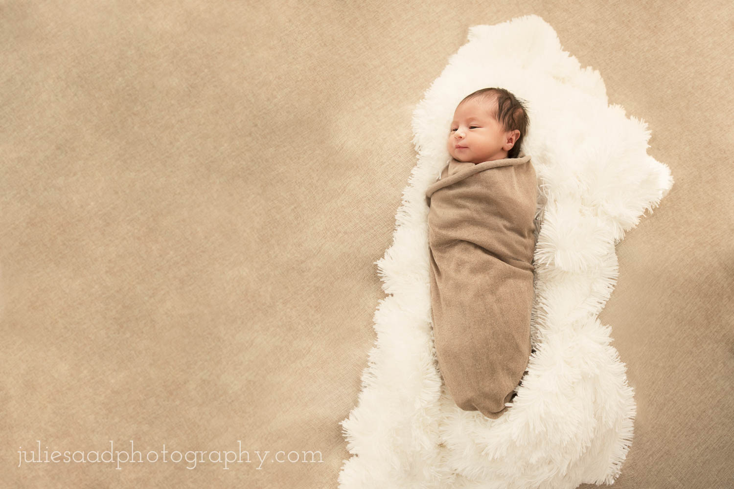 Newborn photography in Brooklyn, NY. Beautiful baby girl swaddled on comfy cotton rug atop burlap backdrop. Creating an image like this with some extra space for text is an excellent idea for birth announcements.