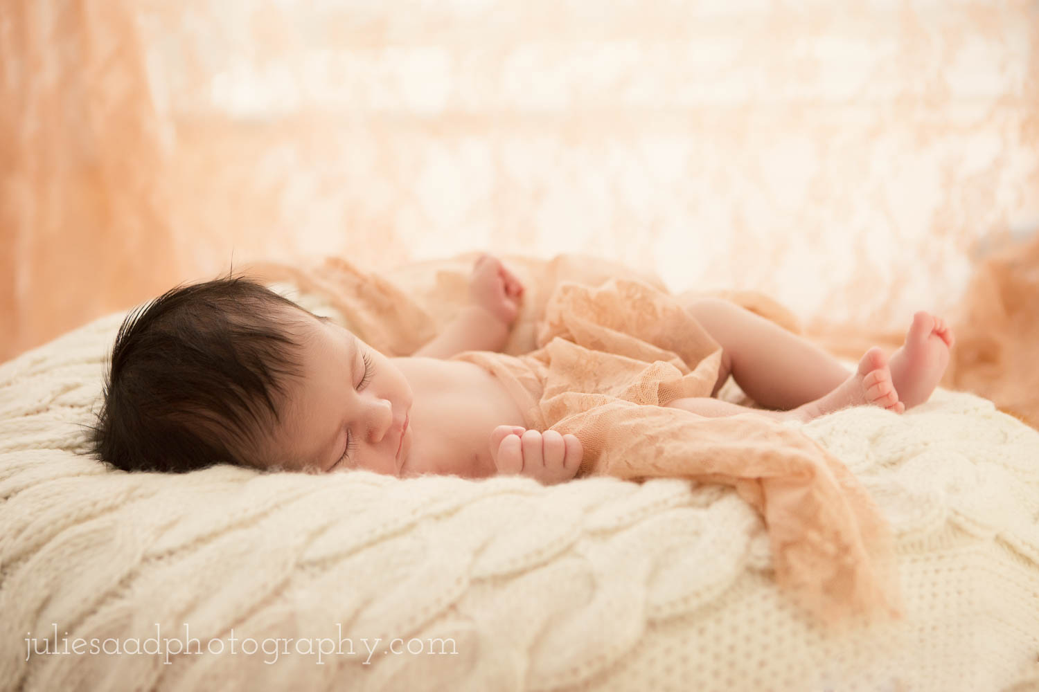 Newborn photography studio in New York. ©2014 Julie Saad Photography. Image of a newborn baby girl sleeping in sunlight.