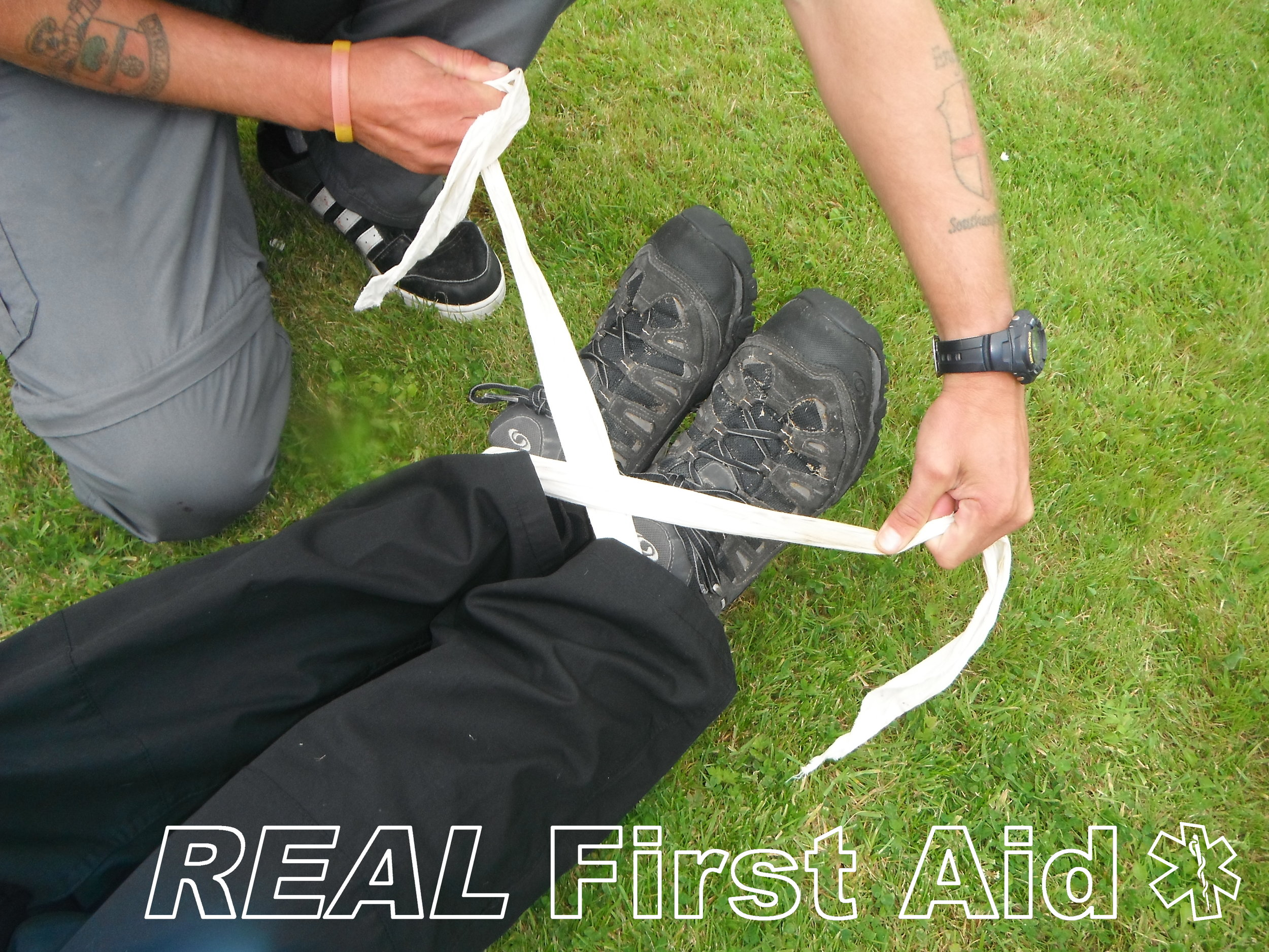 1. Using a triangular bandage or alternative (tape, cord, belt etc) tie the casualty's ankles together; this is most comfortably and stably achieved applying a 'figure of eight' around the back of the casualty's ankles, across their shoe laces and tied off underneath their feet.  Tying the ankles together bring in the feet which prevents outwards rotational forces on the pelvis.
