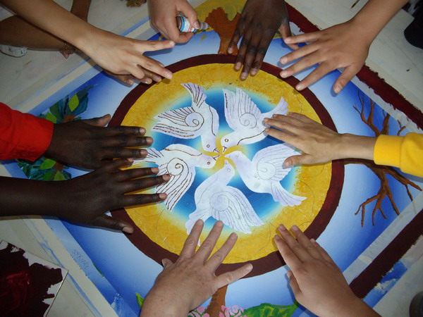 Artist in residence. Children at a primary school create a large mandala for their harmony garden. It reflects a space where there is peace; a safe place to sit and be. This is the center.