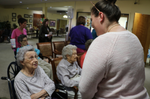 Joy Payne chats and gives a card to a resident of Trinity Home.