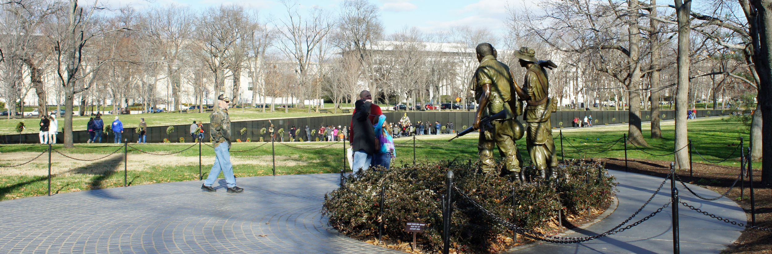 Panoramic view of the Vietnam Veterans Memorial Wall with a partial view the Three Soldiers sculpture in the foreground