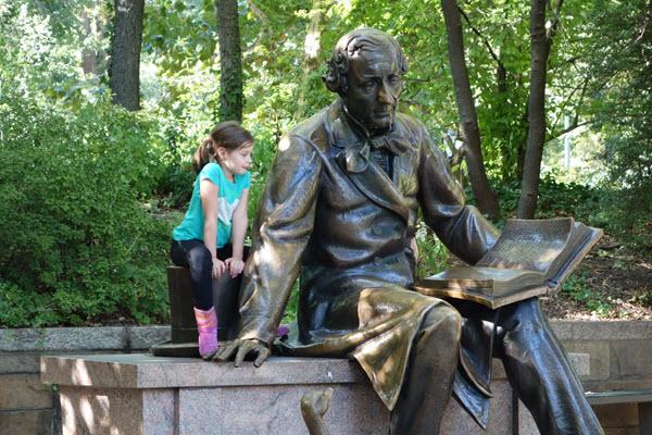 Reading alongside the Hans Christian Andersen statue at New York's Central Park.