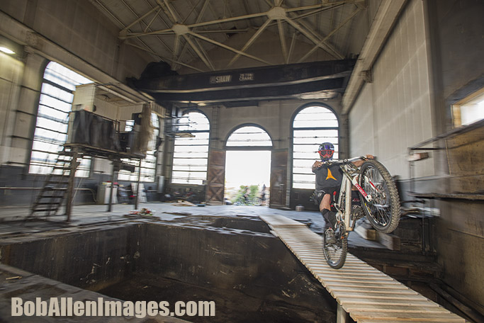 Jed Donnelly rides a wheelie across a ladder bridge in The Con mine at the Evel Urban Downhill practice.